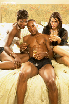 Young man sitting on a bed with two young women